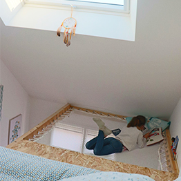 A teen's room under the eaves with a skylight and hammock floor